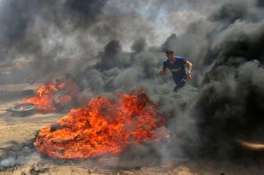 Un palestino camina a través del humo de los neumáticos quemados durante las protestas