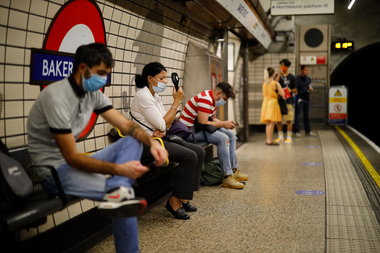 Una mujer usa un ventilador portátil para enfriarse en una plataforma de la estación de metro de Londres el 31 de julio de 2020