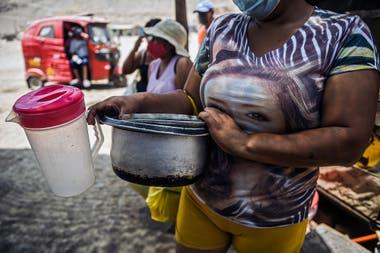 Algunas personas esperan por la comida en un comedor popular en Comas, en las afueras de Lima
