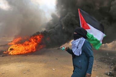 Un palestino lleva la bandera de su país durante las protestas por el traslado de la embajada