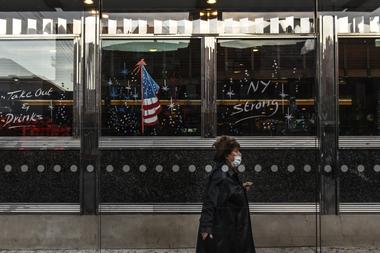 Una persona con mascarilla pasa por el restaurante Bel Aire el 20 de mayo de 2020 en el barrio de Astoria en el distrito de Queens en la ciudad de Nueva York