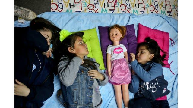 Las niñas Selenna, segunda desde la izquierda, y Mathilda, a la derecha, juegan con una muñeca mientras sus madres asisten a una reunión sobre identidad de género en una librería en Santiago de Chile.
