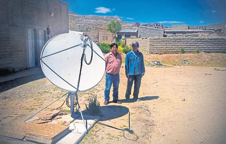 El impulsor: Rufino Llampa (izquierda); comisionado de Mina Pirquitas (Jujuy), y un colaborador junto a una antena satelital; Llampa promovió la llegada de Internet para quebrar el aislamiento