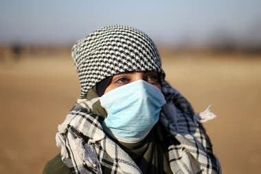 Una joven, ataviada con el tradicional pañuelo palestino, se colocó un barbijo tradicional