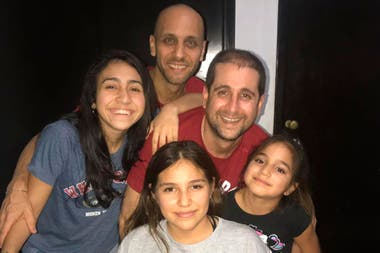 Claudio junto a Fernando, su pareja, y sus tres hijas en su casa en Rosario