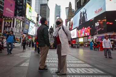 Dos turistas en Times Square utilizan barbijos