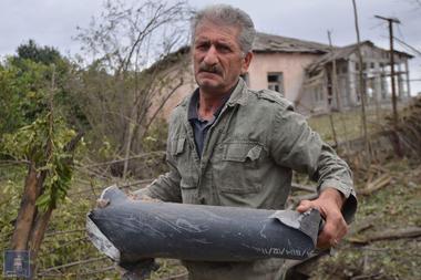 Un hombre sostiene un fragmento de munición tras lo que se dice fue un ataque azerí durante los enfrentamientos entre separatistas armenios y Azerbaiyán en la región de Nagorno-Karabaj