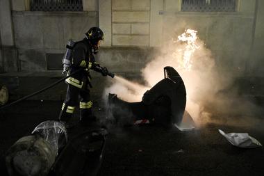 Un bombero italiano apaga un contenedor de basura en llamas durante una protesta de activistas de extrema derecha contra las medidas de restricción del gobierno para frenar la propagación del coronavirus, en el centro de Turín, el 26 de octubre de 2020