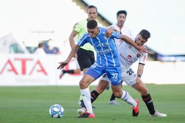 Gonzalo Abrego (Godoy Cruz) intenta llevarse la pelota ante la marca de Julián Fernández, volante central de Newells