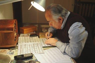 La radio antigua dominando las partituras escritas a mano en la mesa de trabajo de Manolo Juárez