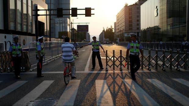 Personal de seguridad impide el paso de un hombre mientras cierran el acceso a West Lake antes de la cumbre del G-20, en Hangzhou