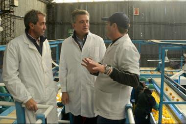 Etchevehere, en el centro, visitó la planta que exportó las mandarinas a China