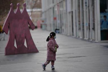 Una niña camina con un barbijo por las calles desoladas de Pekín