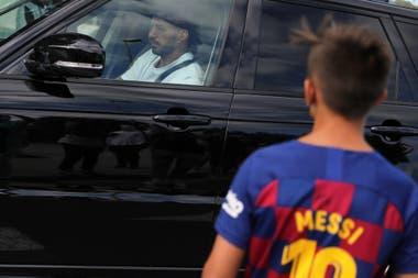 Un niño con la camiseta de Messi ve la llegada de Luis Suárez a las pruebas médicas en la Ciudad Deportiva Joan Gamper