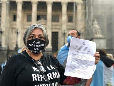Una de las manifestantes exhibe la autorización de la Ciudad para armar la carpa, pero después no le dejaron instalarla