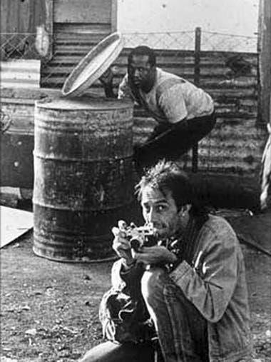 Kevin Carter capturado en acción. Atrás, un poblador se resguarda de las balas (Guy Adams)