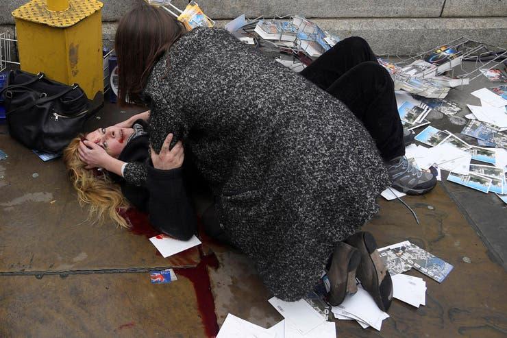 Una mujer herida tirada en la vereda luego del atentado de Khalid Masood, en Londres. Masood atropelló a peatones con su auto, logrando matar a cuatro y a un oficial de policía en el puente de Westminster. 22 de marzo de 2017