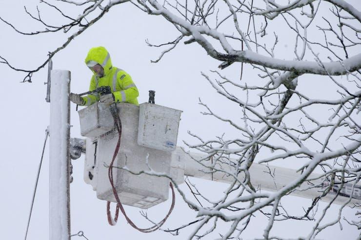 Un hombre repara los cables de electricidad; varias zonas quedaron sin suministro eléctrico
