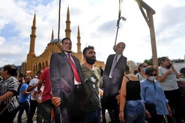 En una protesta en Beirut un hombre posa con una foto del primer ministro libanés, Hassan Diab (izq.), Y el presidente ejecutivo de las Fuerzas Libanesas, Samir Geagea, que aparecen colgados
