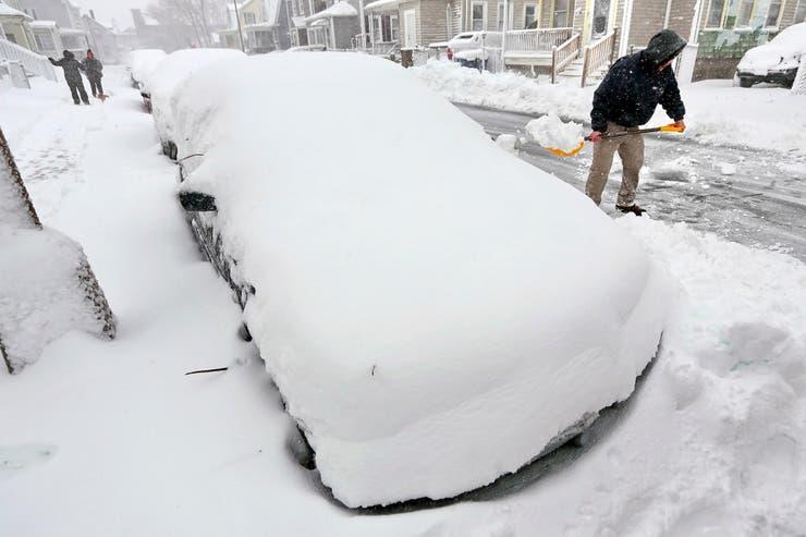 Un hombre quita la nieve de su auto en Bedford, Massachusetts