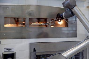 Pazzi arma la pizza con los ingredientes pedidos, la mete al horno, la saca, la corta en porciones y la pone en la caja