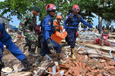 "Indonesian rescue personnel carry away a body bag at the Villa Stephanie accommodation in Carita, Banten province on December 24, 2018, two days after a tsunami - caused by activity at a volcano known as the ""child"" of Krakatoa - hit the west coast of Indonesias Java island. - The death to"