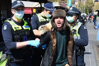 La policía detiene a un manifestante anticuarentena en el mercado Queen Victoria de Melbourne durante una manifestación, el 13 de septiembre de 2020