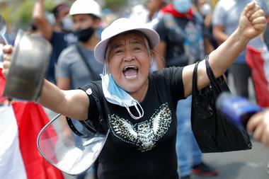 Una mujer celebra afuera del Congreso en Lima luego de que el presidente interino peruano Manuel Merino presentara su renuncia el 15 de noviembre de 2020