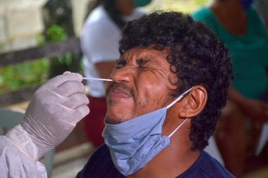 Un trabajador de la salud toma una muestra de hisopado de un hombre en la comunidad ribereña de Bela Vista do Jaraqui, Manaus, estado de Amazonas, Brasil, el 18 de enero de 2021