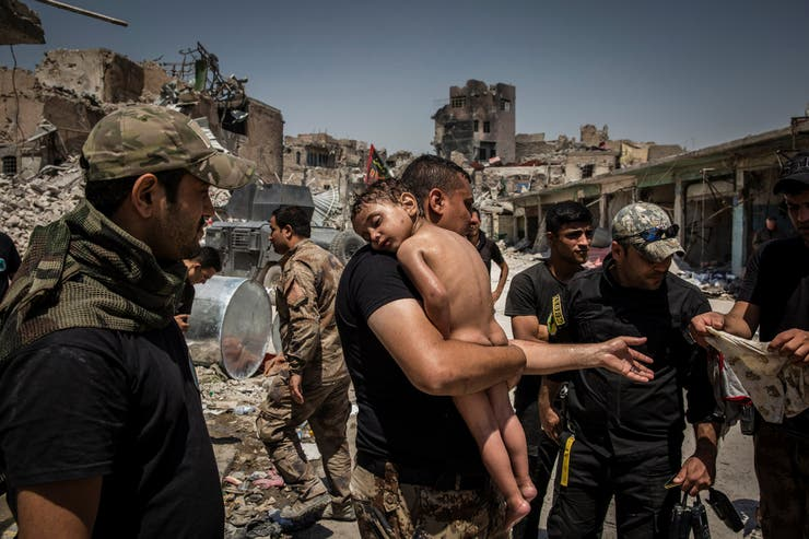 12 de julio de 2017. Un niño no identificado, que fue llevado fuera de la última área controlada por EI, es cuidado por soldados de las Fuerzas Especiales iraquíes.