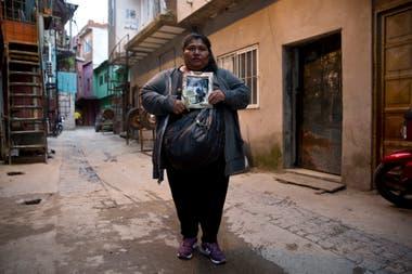 Maria Alejandra Martínez, en la puerta de su casa con la foto de su padre