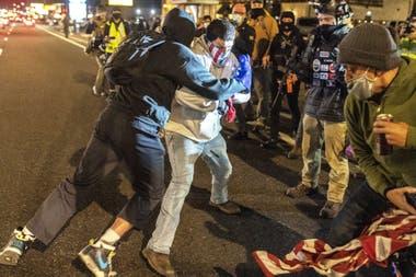 Activistas de Black Lives Matter chocan con un manifestante de derecha después de que la multitud intentara quemar una bandera estadounidense en Washington