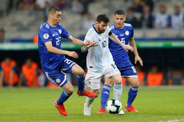 Messi maniobra ante la marca de Miguel Almirón en el último partido entre Argentina y Paraguay