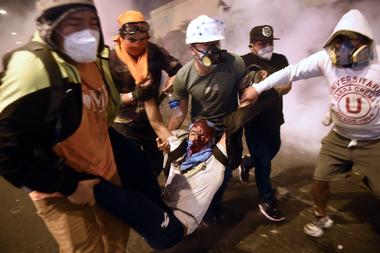 Un manifestante, partidario del derrocado presidente peruano Martín Vizcarra, recibe ayuda de otros manifestantes después de resultar herido durante enfrentamientos con la policía antidisturbios tras una protesta contra el gobierno del presidente interino Manuel Merino en Lima el 14 de noviembre de