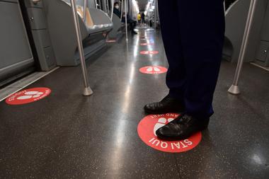 Un hombre se para en un círculo rojo, con el objetivo de mantener la distancia entre los viajeros en una línea de subte en Milán, el 28 de abril de 2020