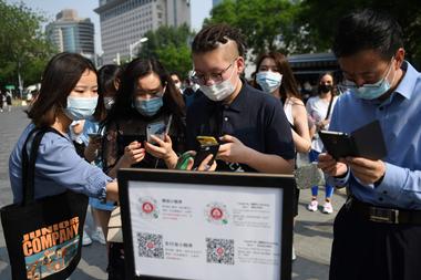 Un grupo de ciudadanos escanea su estado de salud a través de una aplicación de rastreo en Pekín