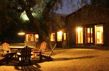 El jardín de La Granadilla junto a la casa con las luces encendidas por la noche.