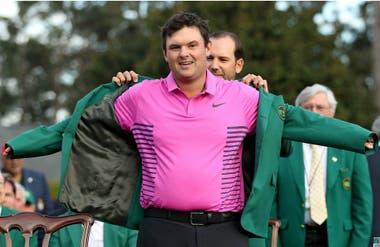 El gesto de felicidad de Patrick Reed, que extiende sus brazos para que Sergio García, el campeón último del Major, le coloque el tradicional saco verde