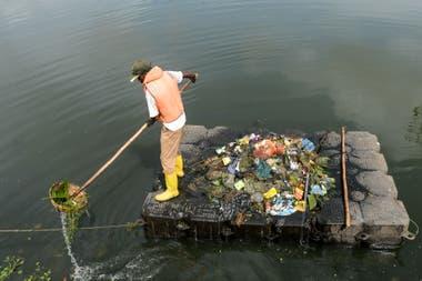Un trabajador recoge basura de un lago en las afueras de Colombo, Siri Lanka