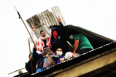 Los presos se asoman a través del techo destruido del penal de Devoto