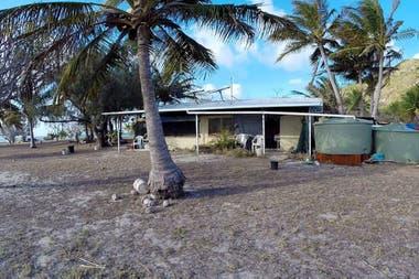 Una foto de la casa de Glasheen en la isla, completa con dos contenedores de almacenamiento que recogen la lluvia para el agua potable.