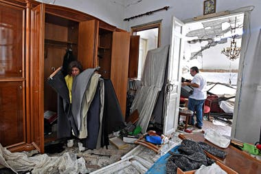 Una mujer inspecciona sus pertenencias en su casa dañada en la capital libanesa, Beirut