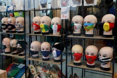 Máscaras protectoras con diseños de banderas se exhiben en una tienda en París