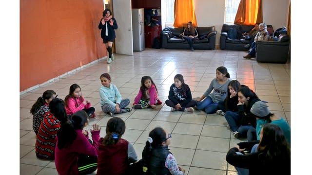 Angela, llegando, arriba y Selenna, sentadas en el círculo en la parte superior izquierda y vistiendo un buzo azul, toman una clase de teatro y danza con chicas en su centro comunitario Santiago de Chile.