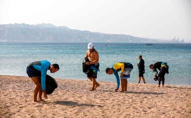 Los surfistas participan en el día internacional de limpieza de playas frente a la ciudad turística de Eila, en el sur del Mar Rojo de Israel