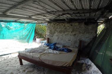 """Glasheen dice que la vida en la isla es """"pacífica, segura y satisfactoria"""". Arriba, su habitación, que tiene un piso de arena estilo náufrago"""