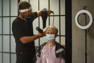 Un peluquero con protección facial peina a una clienta el 11 de mayo de 2020 en una peluquería en Praga