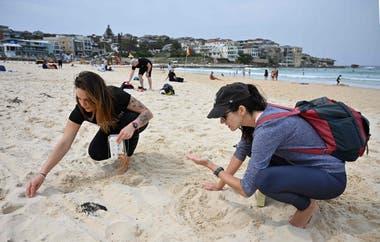 Las activistas Julie Montedoro, de 29 años, e Isabel Young Pérez, de 32, participan en una limpieza de la playa en la playa de Bondi en Sydney