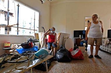 Una pareja trata de limpiar los escombros en su hogar