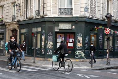 Ciclistas pasan por el bar Au Chat Noir, cerrado como parte de restricciones más estrictas por el coronavirus, en París, Francia
